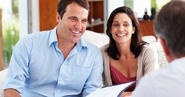 a couple and a realtor drafting a purchase agreement