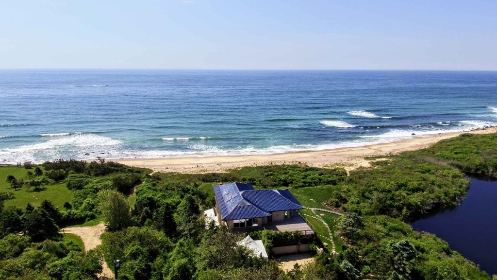This extraordinary property is an oceanfront masterpiece on 36 private and verdant acres in exclusive Montauk Point, the Malibu of the East Coast. The 7,000-square-foot main house is the vision of architect Frank Hollenbeck, who based the design on a Chinese tea house, evidenced in the beautiful pagoda-style blue-tiled roof. It is ideally situated on a high bluff overlooking the Atlantic Ocean and a secluded, sandy beach with no public access for miles. The property includes a two-acre pond which provides habitat for local flora and fauna. At the ocean's edge, two naturally formed 100-foot jetties act as barriers to passing storms.