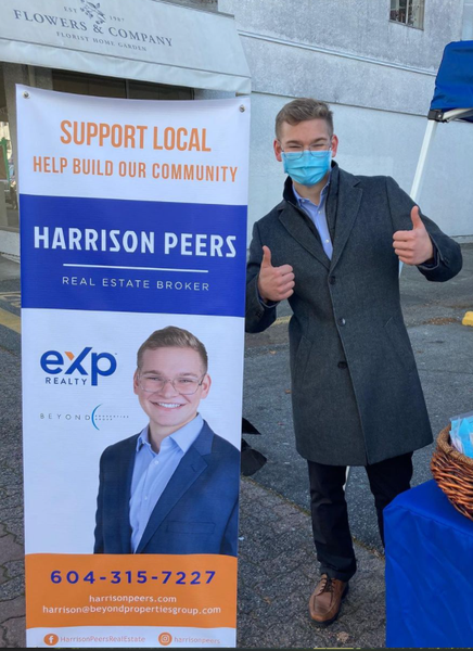 Harrison Peers Realtor posing with his sign in front of Bin 101