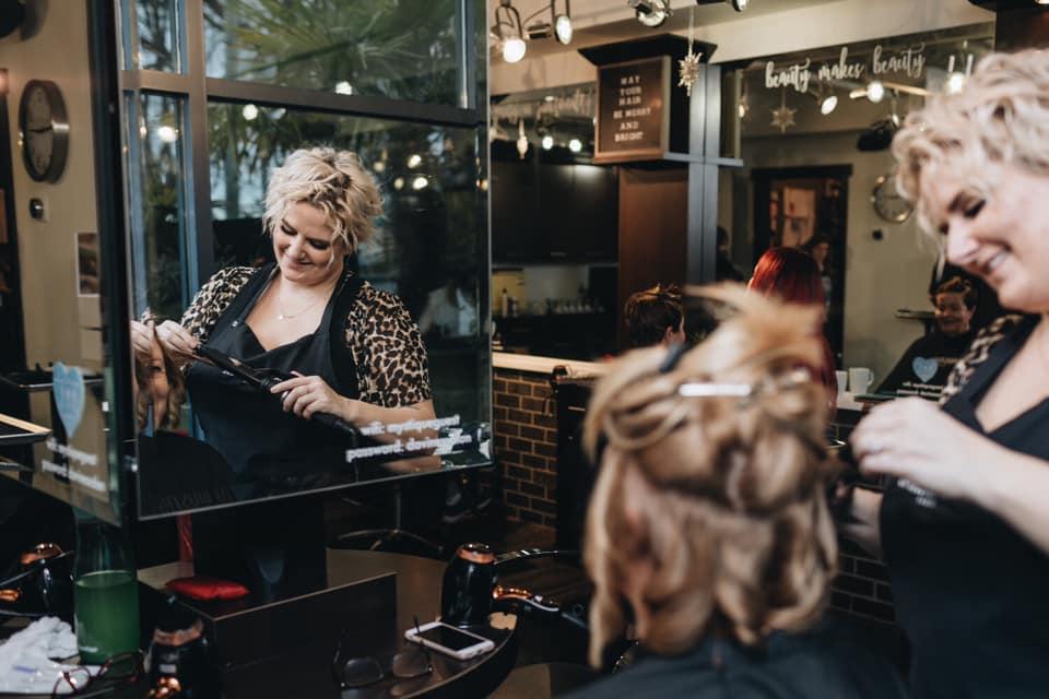 Hair Stylist inside Mystique Hair Design giving a client a hair cut